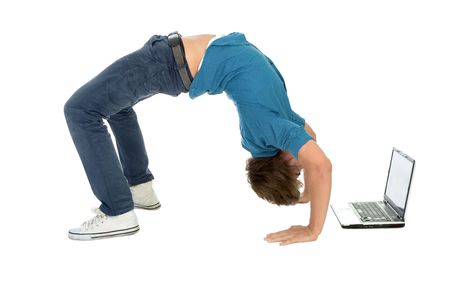 bend over: Young man bending over backwards while using laptop