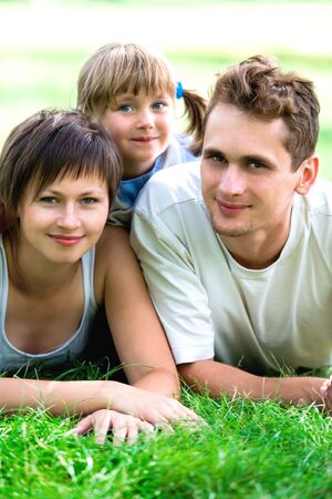 Young Family Lying on the Grass  photo