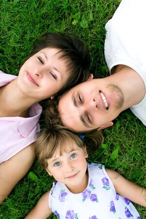 Family lying on grass photo