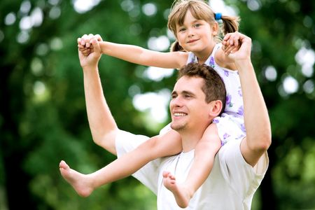 father with children: Father Giving Daughter Piggyback Ride Stock Photo