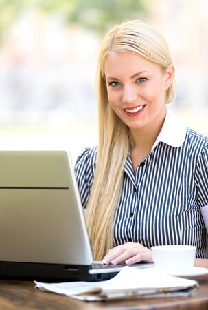 Businesswoman outdoors with laptop photo