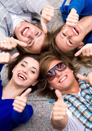 adolescentes chicas: Los adolescentes con los pulgares arriba Foto de archivo