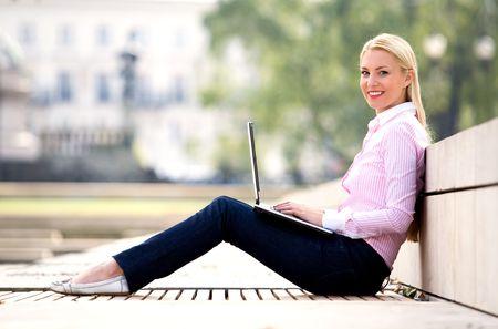Woman using laptop outdoors photo