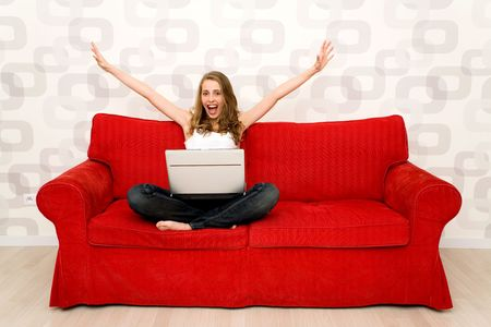 excited: Woman sitting on couch with laptop Stock Photo