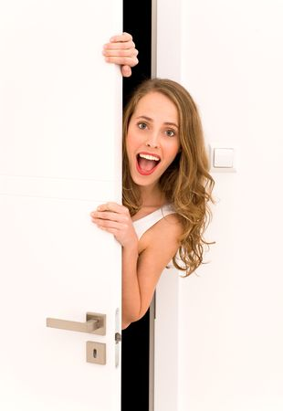 Young woman peeking through door