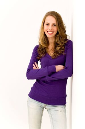Woman leaning on wall and smiling photo