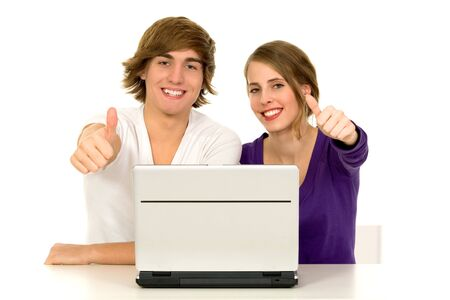 successful student: Couple using laptop showing thumbs up Stock Photo