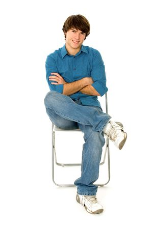persona sentada: Hombre joven sentado en silla  Foto de archivo