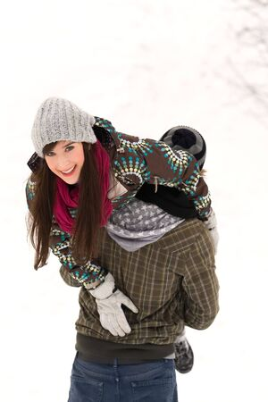 carrying girlfriend: Couple playing in snow