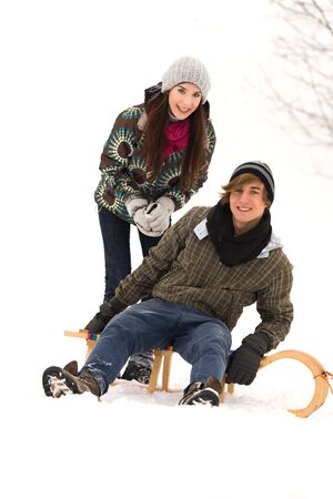 Young couple on sled in snow photo