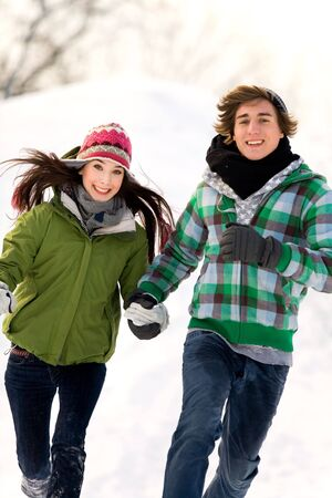 Couple running in the snow photo