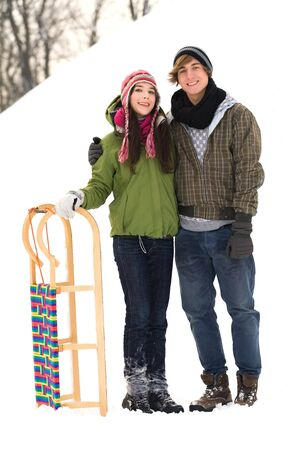 Couple standing in snow by sled photo