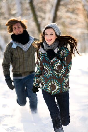 Couple running in the snow Stock Photo - 6280929
