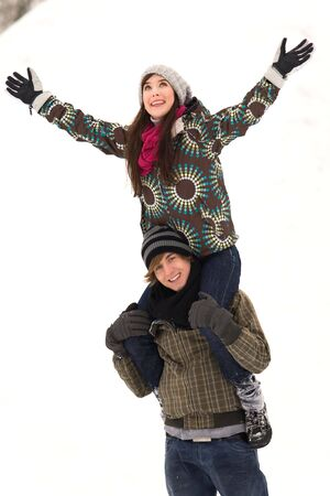 Man carrying woman on shoulders in snow 版權商用圖片