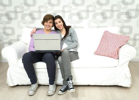 Young couple using laptop on couch photo