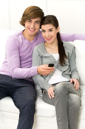 Couple sitting on couch with cellphone photo