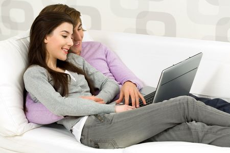 Young couple using laptop on couch Stock Photo - 6389950