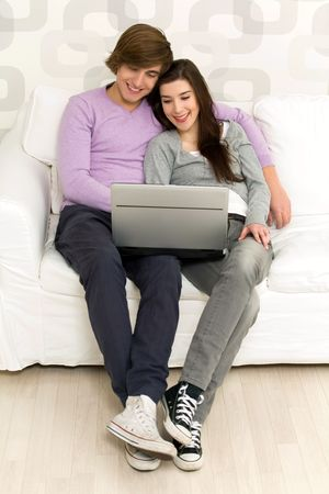 Young couple using laptop on couch Stock Photo - 6389954