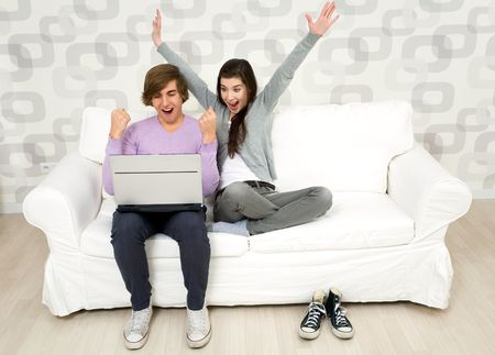 woman laptop happy: Young couple using laptop on couch Stock Photo