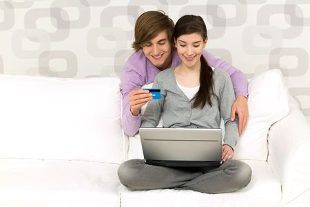 Young couple using laptop on couch Stock Photo