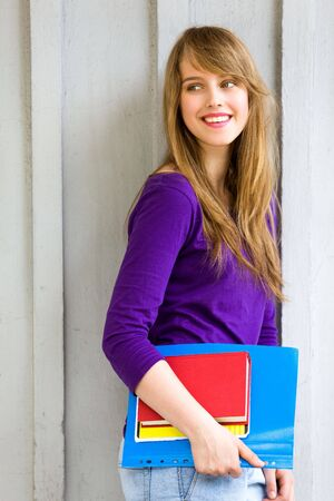 Female student holding books photo