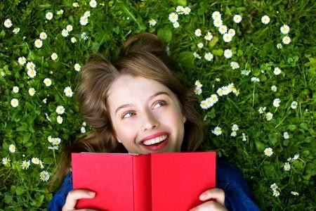 mujer leyendo libro: Mujer tumbada sobre c�sped con libro  Foto de archivo