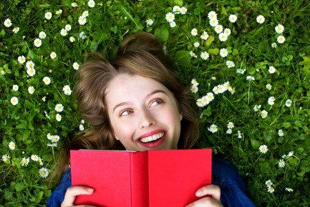 learning to read: Woman lying on grass with book