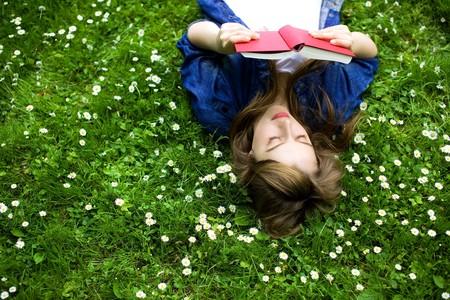 女人躺在草地上,手里拿着书