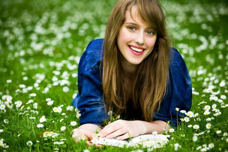 Woman lying on grass with book Stock Photo - 7231528