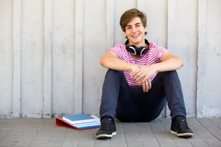 Young man sitting with books photo