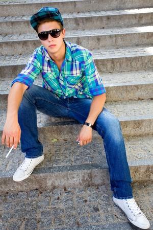 joven fumando: Chico joven sentado con cigarrillo