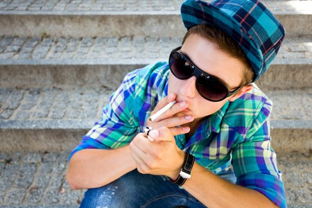 man smoking: Teenager Lighting A Cigarette Stock Photo