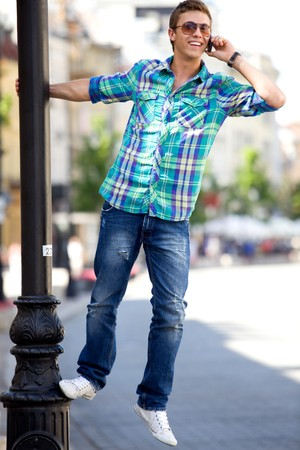 Young man hanging on lamp post Stock Photo - 7367563