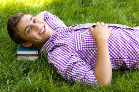 Young man lying on a pile of books in a lawn Stock Photo - 7379947