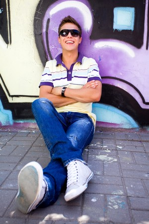 Young man sitting against graffiti wall photo