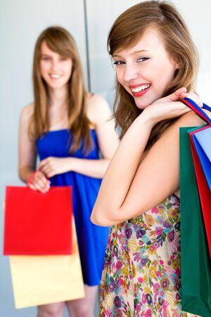 girl bonding: Young women with shopping bags Stock Photo