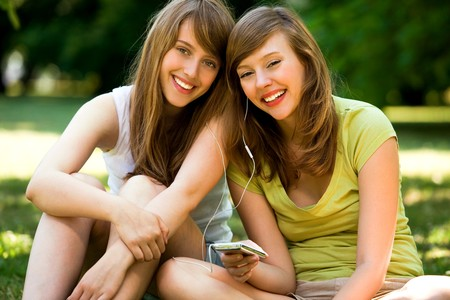 Young women listening to MP3 player photo