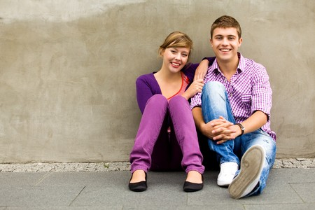 happy teenager: Teenagers sitting by the wall