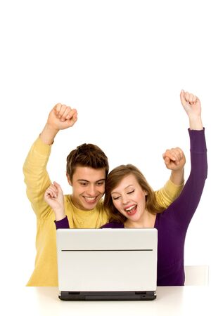 Couple with arms raised using laptop photo