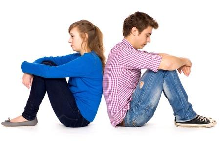 Teenage couple sitting back to back photo