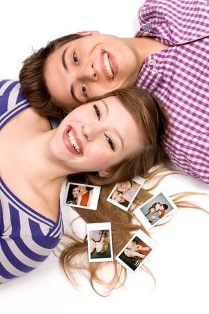 Young couple lying with photos