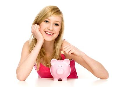 white piggy bank: Woman putting coin in piggy bank
