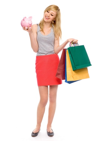 Woman holding piggy bank and shopping bags photo
