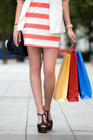 sidewalk sale: Legs and heels of woman with shopping bags