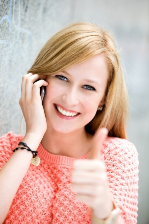 Young woman showing thumbs up photo