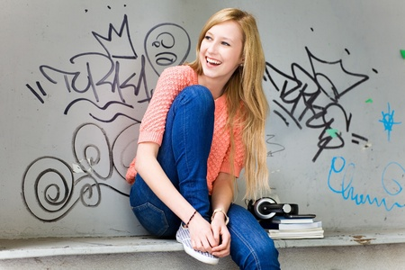 Young woman sitting in front of graffiti photo