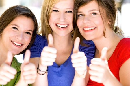 Three girls with thumbs up photo