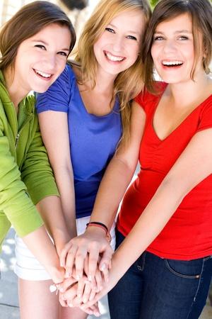 adolescentes riendo: Amigos con las manos juntas Foto de archivo