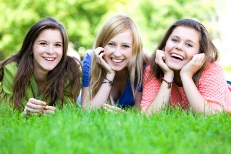 Three girls lying on the grass  photo