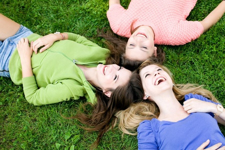 people laughing: Three girls lying on the grass